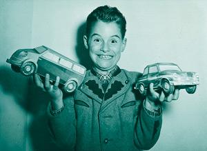 Fotos eines Jungen mit zwei Modellautos in den Händen
